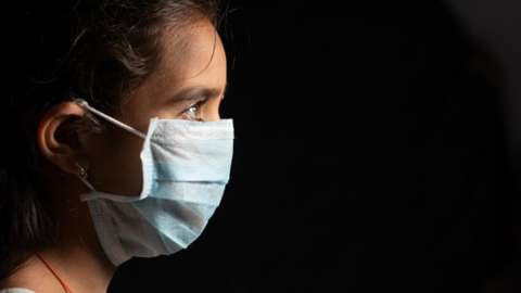 Young teenager girl with medical face mask in dark room at home quarantine due to covid 19 or coronavirus outbreak