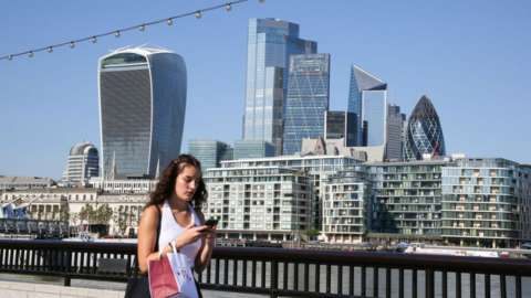 Woman using mobile phone in front of City of London skyline.