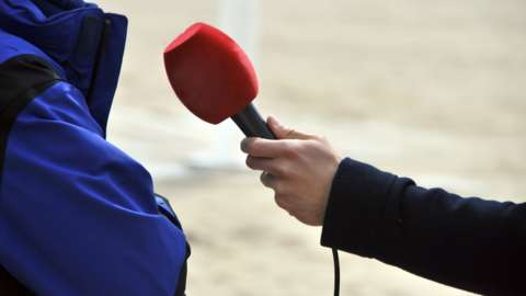 Anonymous person being interviewed with a microphone