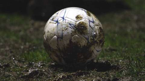 A football is caked in mud