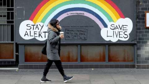 A woman walking past a rainbow mural