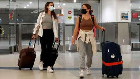 Two women carrying luggage arrive at Miami International AIrport