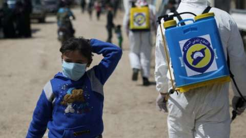 An internally displaced Syrian girl wears a face mask as members of the Syrian Civil defence sanitize the Bab Al-Nour camp