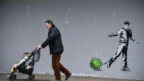 Man walking past graffitti