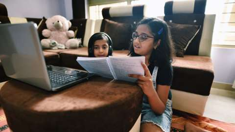 Sisters attending online school using laptop