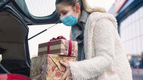 WOMAN PUTTING PRESENTS IN A CAR