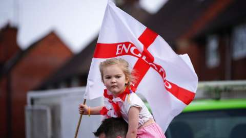 A young girl holds a St George flag at the 2018 Stone Cross St George's Day parade