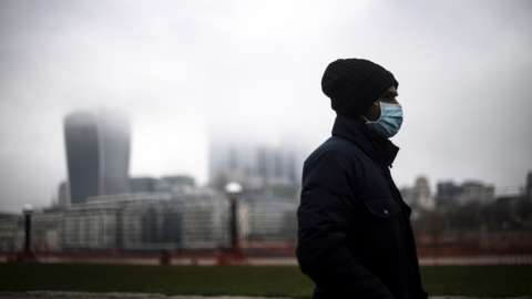 Man walks along south bank of Thames through city of London on a grey day, with a mask on