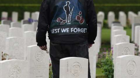 A person stands in a jacket reading 'lest we forget' at a Commonwealth War Graves Commission event in Bayeux, Normandy, France, in 2019.