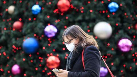 Woman wearing face covering walks past Christmas tree