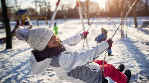 Child on swing in snow