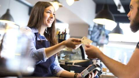 Waitress accepting a customers' payment.
