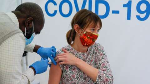 A woman receives a vaccine in a at Newmarket Racecourse