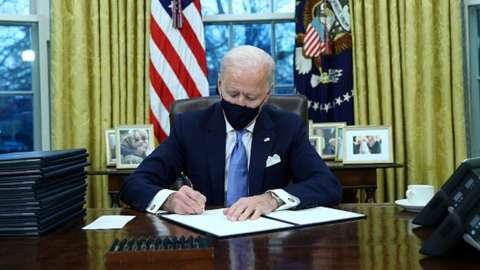 US President Joe Biden signs documents after being sworn-in