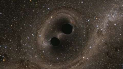 """Artists impression of two black holes locked in a """"death spiral"""""""