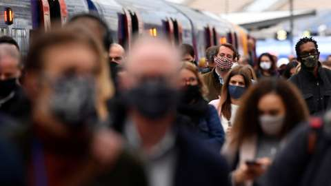 People wearing protective face masks arriving at Waterloo Station