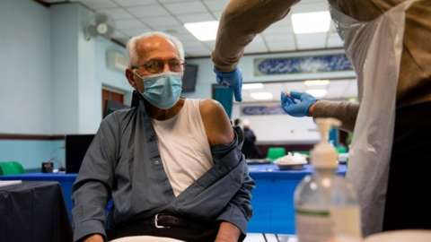 A man wearing a facemask while getting vaccinated