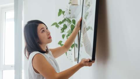Young woman hanging picture frame on wall