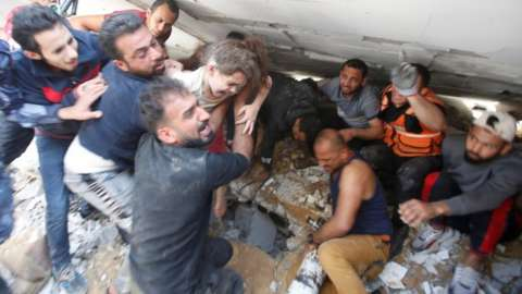 Rescuers carry a girl as they search for victims amid rubble at the site of Israeli air strikes, in Gaza City May 16, 2021.