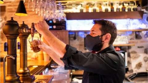 Bartender wearing face mask pulls a pint