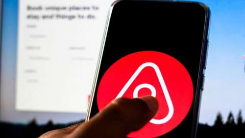 The AirBnB logo on a mobile phone held up in front of a computer screen showing the company's website