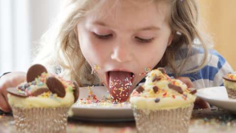 A young girl eats sweets