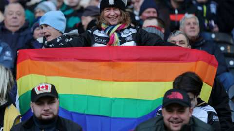 Fan holds up rainbow pride flag at Hull FC's KCOM Stadium for the visit of Catalans Dragons' Israel Folau