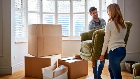A young couple move furniture into a house
