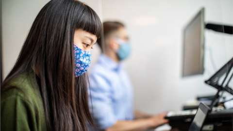 A female worker wearing a mask