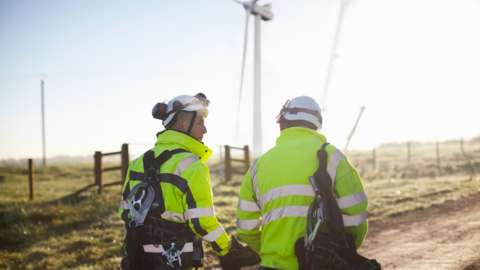 Two engineers at wind farm, walking together