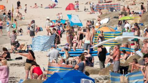 People enjoy the fine weather as they spend time on the beach at Sennen Cove near Penzance
