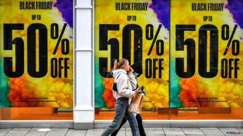 People walk past Black Friday sale signs