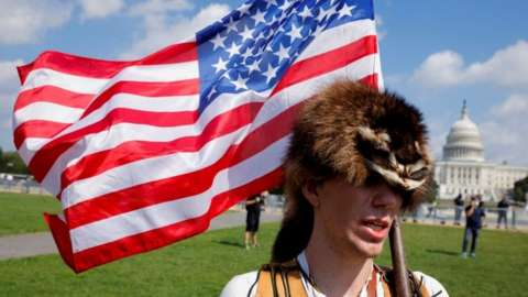 A man wearing a raccoon hat talks about his belief that Donald Trump won the election