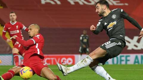 Liverpool's Thiago tries to block a shot by Manchester United's Bruno Fernandes