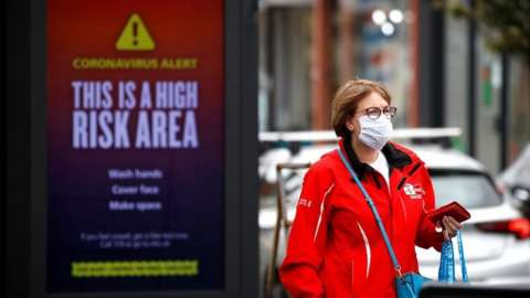 A woman wearing a protective mask walks past a warning sign in Greater Manchester