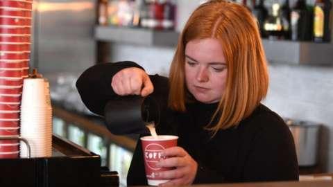 A barista makes a coffee.