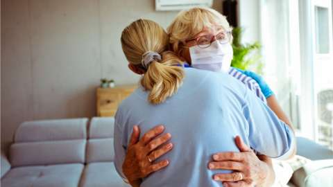 Stock photo of a nurse embracing an elderly woman