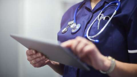 A stock image of a health worker looking at patient records