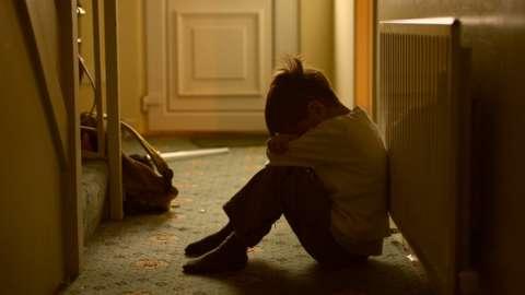 Upset child sitting in hallway
