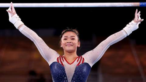 Sunisa Lee smiles with her hands in the air