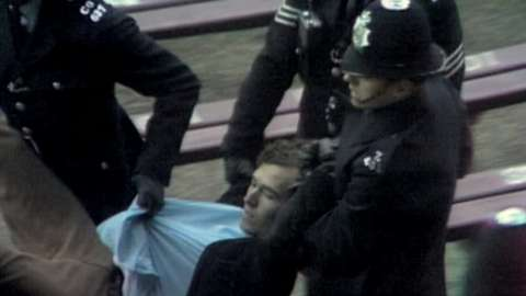 Peter Hain being dragged away by police after invading a sports pitch
