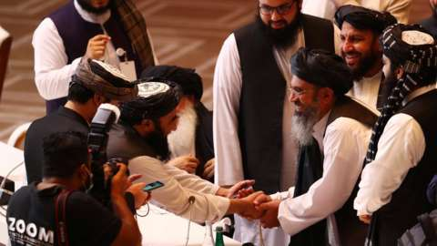 Taliban delegates shake hands during talks with the Afghan government in Doha, Qatar. Photo: 12 September 2020