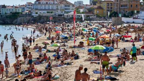 Beachgoers crowd Praia da Duquesa in Cascais, Portugal