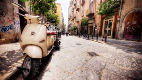 Line of Vespas on an Italian street in the summer