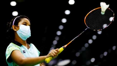A badminton player plays in a mask