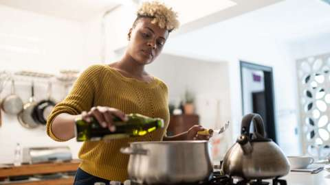 A woman cooking in a kitchen