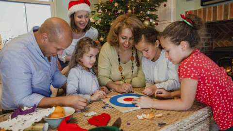 Family playing a Christmas board game