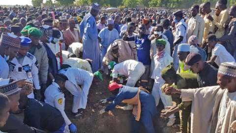 Men gather during the mass burial of people who were killed by militant attack
