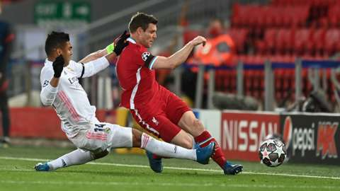 james Milner of Liverpool is fouled by Casemiro of Real Madrid during the UEFA Champions League Quarter Final Second Leg match between Liverpool FC and Real Madrid at Anfield on April 14, 2021