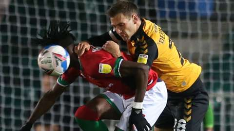 Elijah Adebayo of Walsall and Mickey Demetriou of Newport County compete